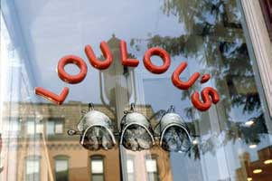Logo on a glace panel part of Loulou's restaurant branding and visual identity | CRA Graphic Design